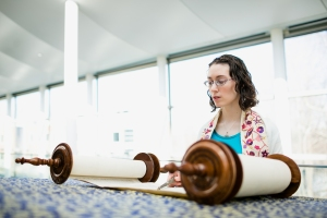 woman reading from a Torah scroll